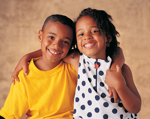 African American brother and sister hold each other and smile for the picture.